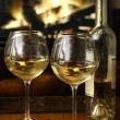 Enjoying glasses of white wine in front of a warm fire — Stock Photo
