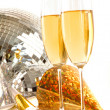 Champagne glass with gold party hats and disco ball — Stock Photo
