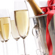 Glasses with Champagne in ice bucket and gift — Stock Photo