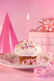Small cupcake with candle, gift and pink party hat — Stock Photo