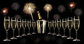 Glasses of champagne with silver ice bucket and fireworks — Stock Photo