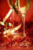 Fluted champagne glasses and ribbons on red — Stock Photo