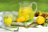 Pitcher of cool lemonade with glass on table — Stock Photo