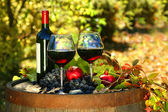 Glasses of red wine on old barrel with autumn leaves — ストック写真