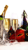Glasses of champagne with masks and party hats — Stock Photo