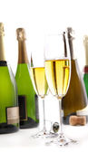Glasses of champagne with bottles on white — Stock Photo