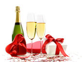 Glasses of champagne with bottle and gifts — Stock Photo