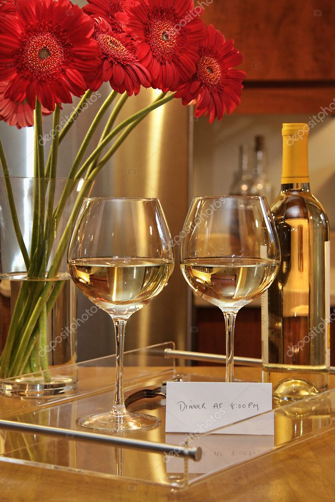 Glasses of white wine with gerbera daisies on counter in the kitchen  — Stock Photo #3278185