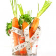 Carrots in a measuring cup with tape measure - Stock Photo