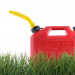 Plastic gas can in grass against white — Stock Photo