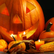 Foto Stock: Scarved pumpkin with candles