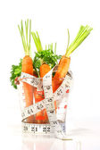 Carrots in a measuring cup with tape measure — Stock Photo