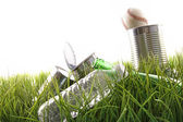 Empty food cans, bottles and baseball in grass — Stock Photo