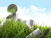 Empty food cans in grass with blue sky — Stock Photo