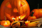 Scarved pumpkin with candles — Stock Photo