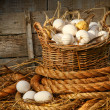Basket of eggs on straw - Stock Photo