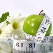 Measurement tape wrapped around green apple - Foto Stock