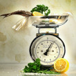 Weight scale with fish and lemons - Stock Photo