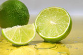Limes on yellow surface — Stock Photo