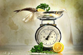 Weight scale with fish and lemons — Stock Photo