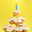 Cupcakes with blue candle on yellow — Stock Photo