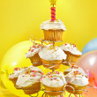 Lots of cupcakes on yellow background — Stock Photo