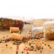 Peppercorns in glass bottles on wood table — Stock Photo