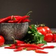 Red peppers and tomatoes with ganite bowl on dark - Stock Photo