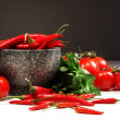 Red peppers and tomatoes with ganite bowl on dark — Stock Photo #3319985