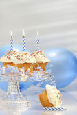 Birthday cupcakes with blue candles — Stock Photo