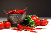 Red peppers and tomatoes with ganite bowl on dark — Stock Photo