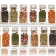 Assorted spices on two layer shelves against white - Stock Photo