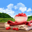 Bowl of raspberries on rustic table - Stock Photo