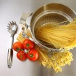 Overhead shot of pasta, tomatoes and pot — Stock Photo