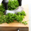 Freshly chopped parsley on wooden cutting — Stock Photo
