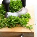 Freshly chopped parsley on wooden cutting — Stock Photo