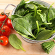 Strainer with spinach leaves and tomatoes — Stock Photo #3320222