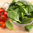Strainer with spinach leaves and tomatoes - Stock Photo