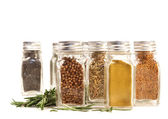 Spice jars with fresh rosmary leaves against white — Stock Photo
