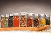 Spices in bottles with wooden spoon — Stock Photo