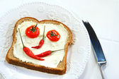 Food arranged into a smiley face on sandwich — Stock Photo