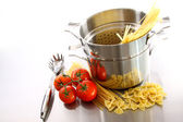 Cooking pot with uncooked pasta and tomatoes — Stock Photo
