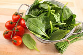 Strainer with spinach leaves and tomatoes — Stock Photo