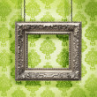 Silver picture frame hung against floral wallpaper background - Stock Photo