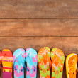 Brightly colored flip-flops on wood - Stockfoto
