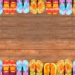 Brightly colored flip-flops on wood - Foto Stock