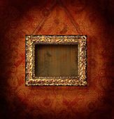 Golded picture frame on antique wallpaper — Photo