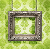 Silver picture frame hung against floral wallpaper background — Stock Photo