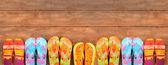 Ahşap üzerine parlak renkli parmak arası terlik — Stok fotoğraf