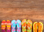 Brightly colored flip-flops on wood — Stock Photo